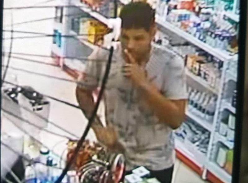 Câmera flagrou o momento que o criminoso fez menção de estar armado, ameaçou o funcionário e, então, levou o dinheiro.(Foto:Reprodução)