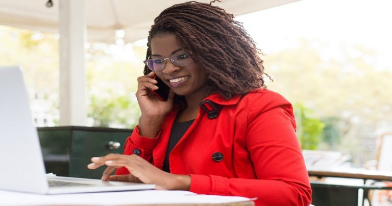 Cheerful woman using laptop and smartphone. Attractive young businesswoman talking by cell phone and using laptop computer in outdoor cafe. Remote work concept